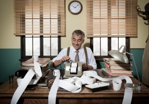 Busy vintage accountant with adding machine surrounded by cash register tape.